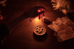 Hand casting magic spell. Witch doing ritual for money. Pentagram, stones and other occult equipment on the table.