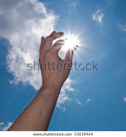 hand catch the sun on blue sky background