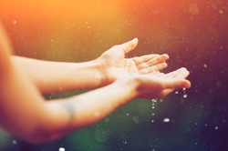 hand catching rain drops on blurred background. Woman hands praying for blessing from god on sunset. Empowerment, sacred forgiveness, positive arm energy, good morning, reborn change calm zen concept.