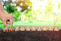 Hand changing impossible to possible wooden blocks in natural background at sunrise. Positivity, nothing is impossible, business success, motivation, achievement and inspiration concept.
