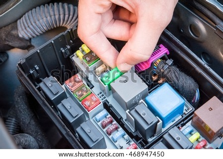 hand checking a fuse in the fuse box of a modern car engine stock hand checking a fuse in the fuse box of a modern car engine