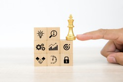 Hand choose king chess on wooden toy blocks stacked with graph and business planning icon. Concepts of business team strategic plan to growth and organization management.