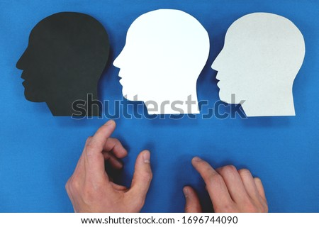 Hand choosing between three versions of self in human head silhouette. Personality and identity crisis concept. ストックフォト ©