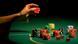 Hand choosing chip on poker table, gambler worrying, afraid to lose all-in bet