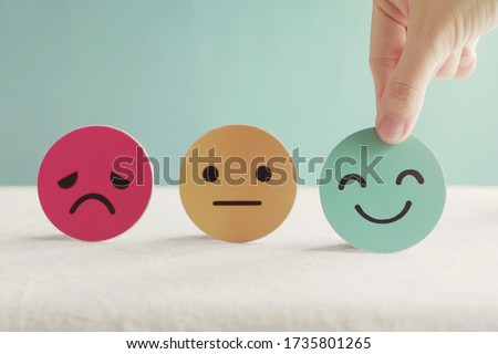 Photo of  Hand choosing happy smile face paper cut, good feedback rating and positive customer review, experience, satisfaction survey ,mental health assessment, world mental health day concept