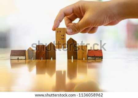 Hand choosing mini wood house model from model and row of coin money on wood table, selective focus, Planning to buy property. Choose what's the best. A symbol for construction ,ecology, loan concepts
