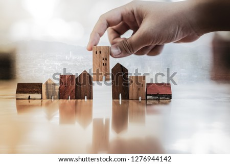 Hand choosing mini wood house model from model on wood table, selective focus, Planning to buy property. Choose what's the best. A symbol for construction ,ecology, loan concepts