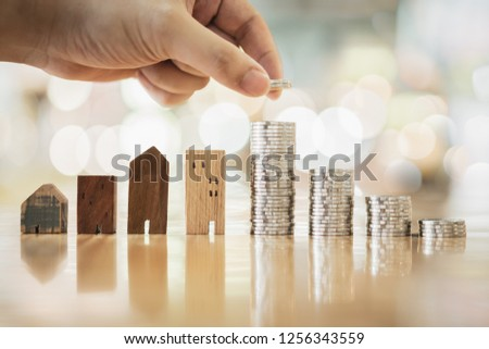 Hand choosing row of coin money on wood table and mini wood house, selective focus, Planning to buy property. Choose what's the best. A symbol for construction ,ecology, loan concepts