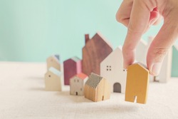 Hand choosing yellow miniature house, searching perfect property in high demand housing boom, choosing best house insurance, making right decision on home investment concept