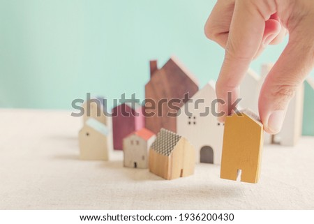 Hand choosing yellow miniature house, searching right property in high demand housing boom, making decision on home investment concept