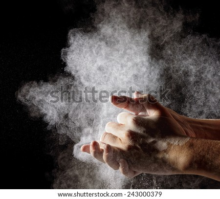 hand clap and white flour on black background
