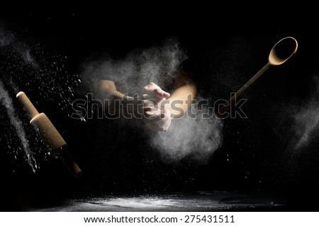 hand clap of chef with wooden rolling pin and spoon in the air with splash flour on black background