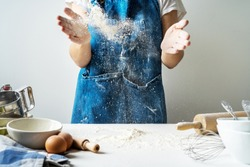 Hand clap of professional women baker  chef with bowl for cooking and baking utensils with splash flour on white background