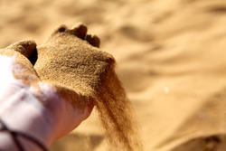 Hand clasping golden sand falling through the finger, with place for text