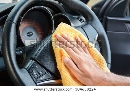 Hand cleaning car steering wheel with microfiber cloth, auto detailing (valeting) concept