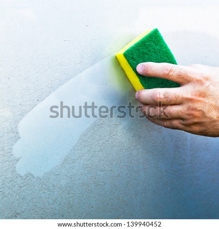 hand Cleaning car using a yellow cleaning sponge