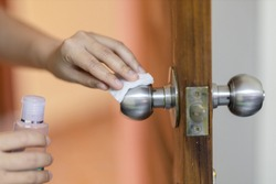 Hand cleaning door knob with alcohol. Corona virus or bacteria infected protection. selective focus have noise.