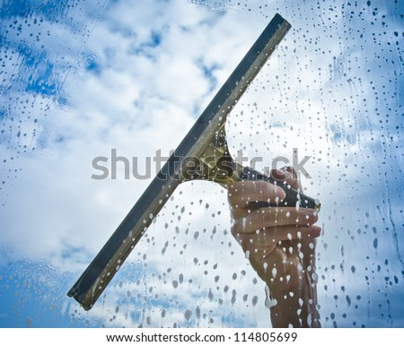 Hand cleaning window with blue sky and white clouds
