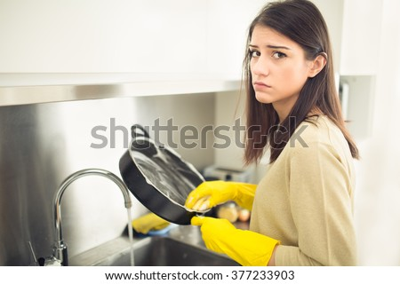 Hand cleaning.Young housewife woman washing dishes in kitchen.Young brunette woman washing dishes manually,by hand,wearing yellow cleaning rubber gloves.Tired of cleaning,making a sad face