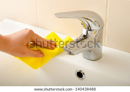 hand cleans tap with sponge