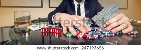 Hand close up. A man in a business suit sitting at the game table. Male player. Passion, cards, chips, alcohol, dice, gambling, casino - it is as male entertainment. Dangerous fun card game for money.
