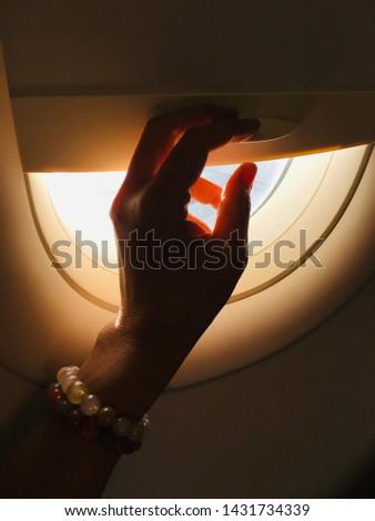 Hand closing the airplane window shade. #1431734339