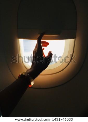 Hand closing the airplane window shade. #1431746033