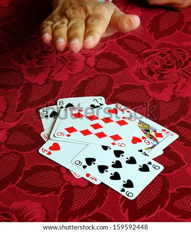 Hand coming down on card game of snap.