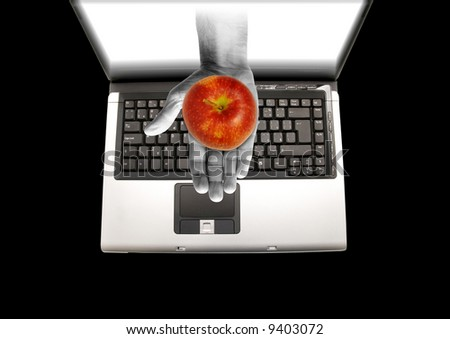 hand coming out of a laptop screen holding a red apple