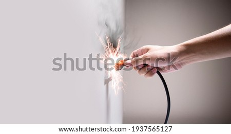 Hand connecting electrical plug cause electric shock, Idea for causes of a home fire, Electric short circuit, Electrical hazard can ignite household items, Residential building electrical fires.