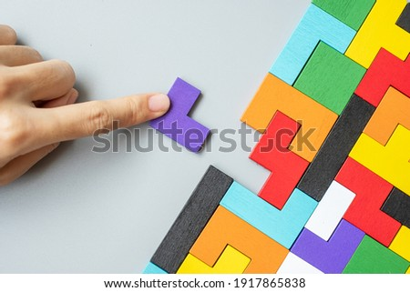 hand connecting geometric shape block with colorful wood puzzle pieces. logical thinking, business logic, Conundrum, decision, solutions, rational, mission, success, goals and strategy concepts Сток-фото ©