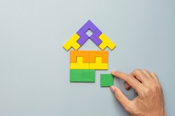 hand connecting Home shape block with colorful wood puzzle pieces on gray background. logical thinking, business logic, solutions, rational, house, real estate and strategy concepts