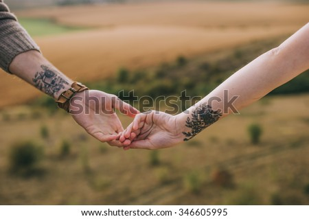 hand couples with identical tattoos