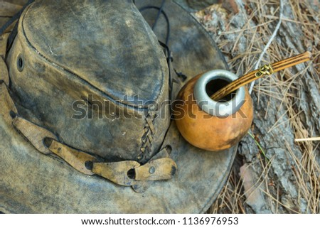 Hand Crafted Artisanal Yerba Mate Tea Leather Calabash Gourd with Straw Hat on Wood Logs in Forest. Travel Wanderlust Concept. Earthy Tones. Traditional Argentinian Latin American Brewing Cup