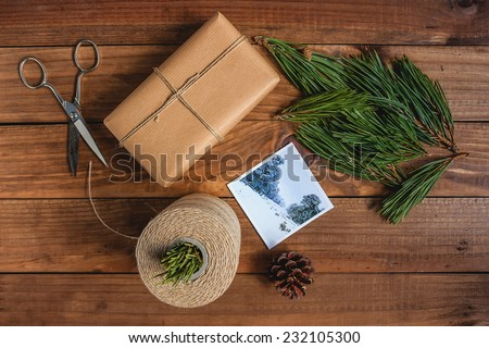 Hand crafted gift on rustic wooden background with Christmas decoration.