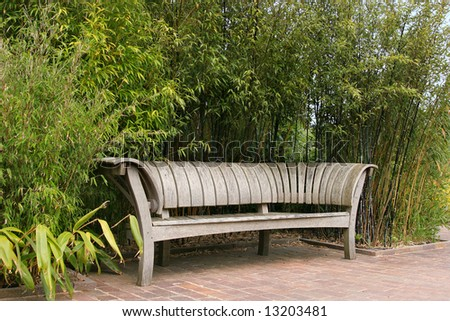 Hand crafted Japanese wooden oak curved seat, standing on a tiled patio terrace with bamboo plants to the rear.