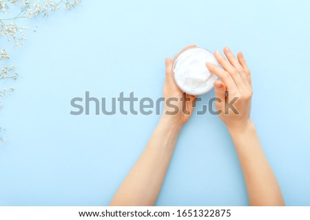 Hand cream, female hands applying organic natural cream cosmetics on a pastel blue colored background. Skin care cream in jar for hands,body. Flat lay moisturizing cream for soft skin, health, beauty.
