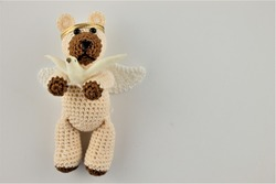 hand crocheted Christmas teddy bear angel holding a dove with copy space to the right