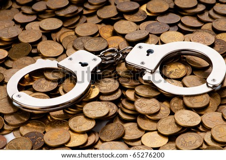 Hand cuffs and coins as security concept
