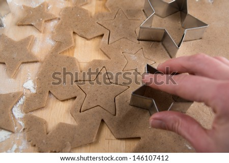 Hand Cutting Out Shapes from Rolled Out Ginger Cookies Dough with Star Cutters