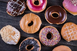 Hand decorated artisan donuts on wooden rustic table, from above