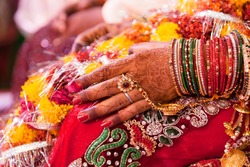 Hand detail of indian bride with decorative bangle and gold ring.