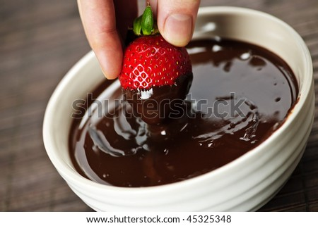 Hand dipping fresh strawberry in melted chocolate