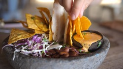 Hand dipping nacho in vegan creamy sous. Healthy vegan Mexican bowl with salsa, beans and dips
