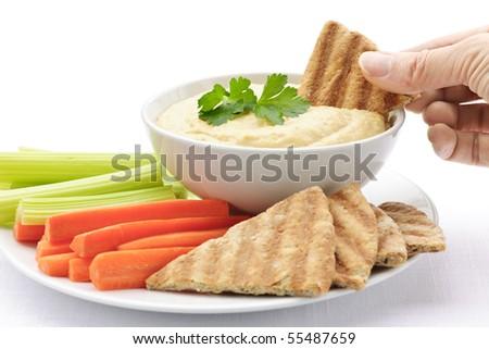 Hand dipping slice of pita bread into bowl of hummus