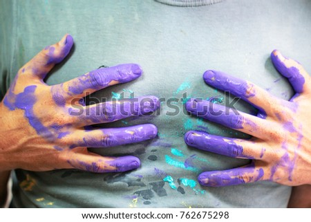 Hand dirty with purple paint on the grey shirt as artist concept and art cretive color house artwork and decorater background