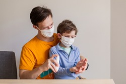 Hand disinfection with an antiseptic. Antibacterial spray sanitation of surfaces from the coronavirus covid-19 virus. Dad teaches his son hygiene. People family in medical masks. Pandemic protection