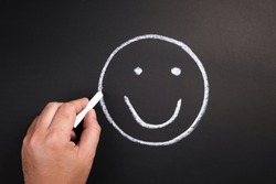 Hand draw a smile face on chalkboard for satisfaction concept