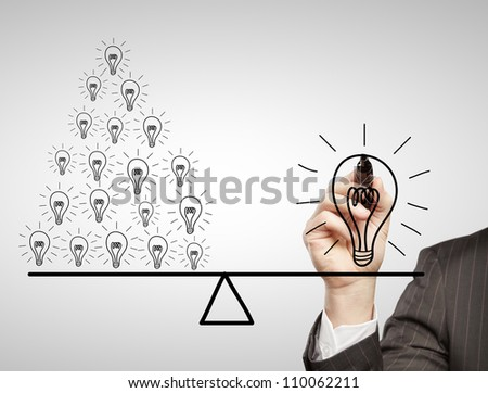 hand drawing a contrast of light bulbs - stock photo