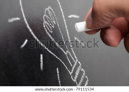 Hand drawing a lightbulb on a chalkboard symbolizing ideas, inspiration and creativity